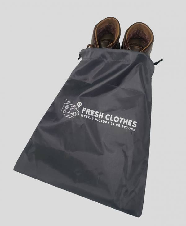 a pair of brown leather shoes halfway sticking out of a grey fresh clothes shoe bag